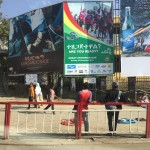 People walking under huge advertisements in downtown Addis.