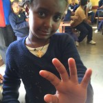A young girl waves to the camera at the Victory School for the Deaf.