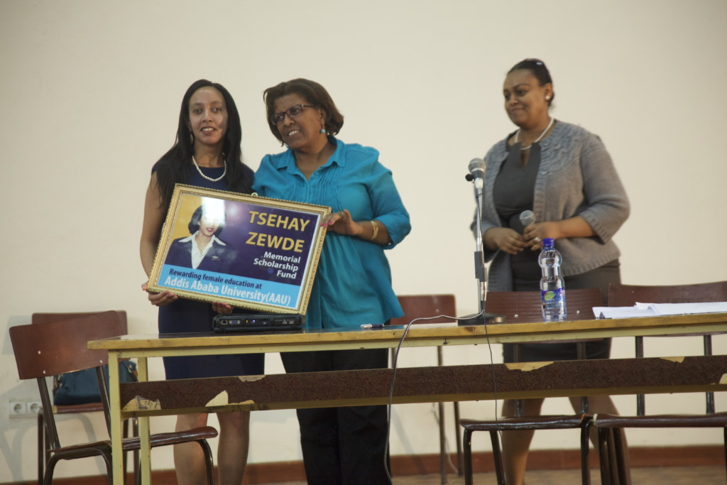 Aster and Haben holding a portrait of Tsehay Zewde at Addis Ababa University event.